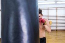Молодий хлопець тренування в тренажерному залі з удар сумка — стокове фото