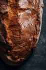 Nahaufnahme von hausgemachtem rustikalem Brotlaib auf dunklem Hintergrund — Stockfoto
