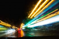 Abstract view of bright trail lights through automobile window at night — Stock Photo