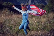 Boy jumping with American flag in nature — Stock Photo