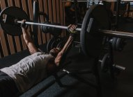 Черный мужчина поднимает тяжелую штангу в спортзале — стоковое фото