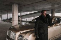 Fiducioso uomo d'affari afroamericano in elegante cappotto in piedi vicino veicolo di lusso sul parcheggio e parlando su smartphone — Foto stock