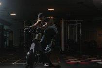 Серьезный черный мужчина на велотренажере в спортзале — стоковое фото