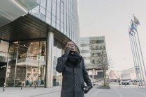 Bello uomo afroamericano in eleganti vestiti caldi gesticolando e parlando su smartphone mentre in piedi sulla strada della città moderna — Foto stock