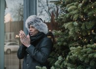 Hombre afroamericano guapo con ropa de abrigo frotándose las manos mientras está de pie cerca del árbol de Navidad con luces de hadas en la calle de la ciudad - foto de stock