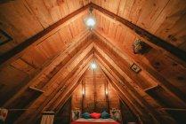 Comodo letto con coperta calda e cuscini morbidi sotto lampade insolite in soffitta accogliente di casa di legname — Foto stock