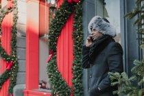 Uomo afroamericano in abiti caldi parlando su smartphone mentre in piedi sulla strada della città vicino alla costruzione e albero di conifera decorato per Natale — Foto stock