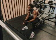 Black man in earphones sitting on exercise machine — Stock Photo