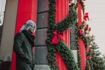 Uomo afroamericano in abiti caldi mentre in piedi sulla strada della città vicino alla costruzione e albero di conifera decorato per Natale — Foto stock