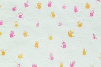 Mão rosa e amarela imprime superfície de decoração da parede de estuque branco — Fotografia de Stock