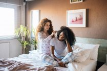 Женщина расчесывает волосы другой девушки в постели — стоковое фото