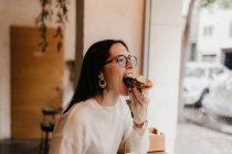 Молода жінка, кусатися смачний бутерброд, сидячи біля вікна в затишному кафе — стокове фото
