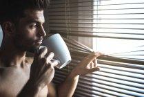Homem atencioso em pé junto a uma janela cega com uma xícara de café — Fotografia de Stock