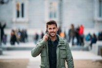 Молодий чоловік на мобільному телефоні і під час зими блукає божевільною — стокове фото