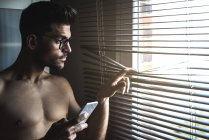 Shirtless man standing by a windows blinds on the mobile phone — Stock Photo