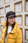Thoughtful young woman in trendy outfit looking away while standing near weathered wall on city street — Stock Photo