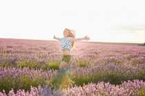 Jovem correndo entre campo de lavanda violeta — Fotografia de Stock