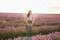 Young woman standing between violet lavender field — Stock Photo