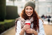 Beautiful redhead woman drinking coffee in the streets of Madrid on winter — Stock Photo