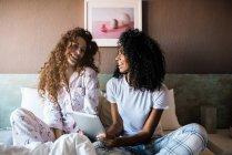 Молодые женщины в постели развлекались на планшете — стоковое фото