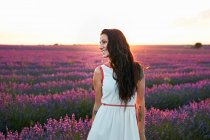 Woman standing between big violet lavender field at sunset — Stock Photo