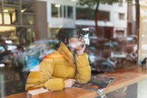 Dreamy young woman in stylish outfit sitting with magazine behind window glass in cafe — Stock Photo