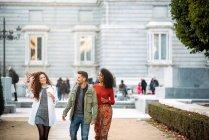 Tre giovani amici che passeggiano e bevono caffè per le strade di Madrid in inverno — Foto stock