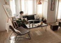 Donna che disegna su carta su divano in camera — Foto stock