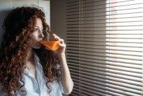 Красивая женщина, стоящая у окон слепая, пьет апельсиновый сок — стоковое фото