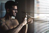 Hemdloser Mann steht vor Jalousien am Handy — Stockfoto