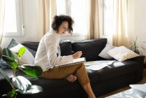 Woman writing on paper on sofa in room — Stock Photo
