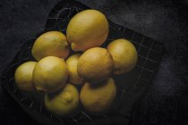 Heap of fresh lemons on napkin on dark background — Foto stock