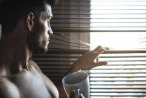 Вдумчивый человек, стоящий у окон, слепой с чашкой кофе — стоковое фото