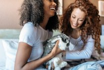 Young women in bed playing with little bunny — Stock Photo