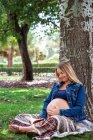 Giovane signora incinta allegra in abbigliamento casual che tiene pancia e seduta sull'erba sotto il legno nel parco verde — Foto stock