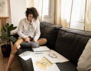 Femme utilisant un ordinateur portable près dessine sur les papiers sur le canapé dans la chambre — Photo de stock