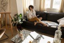 Donna che scrive su carta sul divano in camera — Foto stock