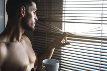 Thoughtful man standing by a windows blind with a cup of coffee. - foto de stock