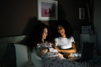 Young cheerful friends in bed entertained on their computer watching movies by night — Stock Photo