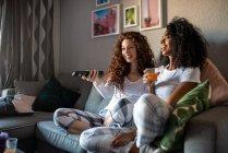 Молодые весёлые подруги сидят на диване и смотрят телевизор. — стоковое фото