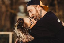 Bearded man embracing cheerful woman near wood in forest on blurred background — Stock Photo