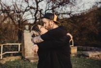 Vista lateral do homem barbudo abraçando e beijando mulher em óculos no parque no fundo borrado — Fotografia de Stock