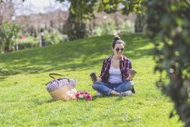 Front view of a young hipster woman wearing sunglasses, sitting on grass in a park while using a mobile phone — Stock Photo