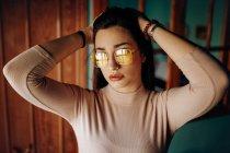 Современная привлекательная очаровательная женщина в розовом свитере с руками на голове в комнате — стоковое фото