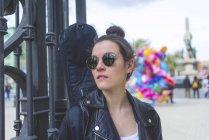 Vista frontale di una giovane donna hipster ridente in piedi e appoggiata su una recinzione nel parco durante la giornata di sole mentre guarda altrove — Foto stock