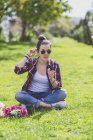 Front view of a young hipster woman sitting on grass in a park while holding a flower in a sunny day — Stock Photo