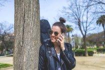Вид сбоку на молодую смеющуюся хипстершу, стоящую и опирающуюся на дерево в парке в солнечный день, используя мобильный телефон — стоковое фото