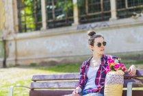 Frontansicht einer jungen Hipster-Frau, die an einem sonnigen Tag auf einer Parkbank sitzt und wegschaut — Stockfoto