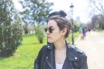 Vista frontale di una giovane donna hipster sorridente che cammina in un parco nella giornata di sole mentre porta una chitarra sul retro e distoglie lo sguardo — Foto stock