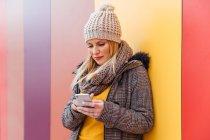 Ritratto di ragazza bionda che scrive sul suo telefono appoggiata a un muro colorato — Foto stock
